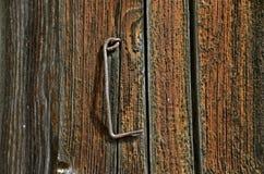 Antiker rostiger Haken hängt an einer Tür lizenzfreies stockfoto