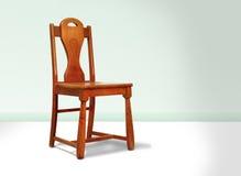 Antiker roter hölzerner Stuhl gegen eine grüne Wand Lizenzfreies Stockbild