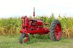 Antiker roter Traktor und Mais Stockbild