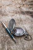 Antiker Uhr- und Tintenstift auf verwittertem Hintergrund Stockbild