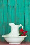 Antiker Wasserpitcher und -becken mit roten Blumen durch rustikalen grünen hölzernen Hintergrund Stockfoto