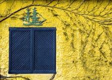 Antikes blaues Fenster gegen gelbe Wand in Spanien Lizenzfreie Stockfotos