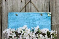 Antikes blaues Zeichen mit Frühlingsblumen- und hölzernemherzen Stockbild