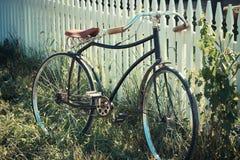 Antikes Fahrrad, das auf einem Zaun sich lehnt Stockfotos