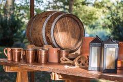Antikes Fass, Brown-Schalen, Lampen und kupferne Gläser auf Holztisch lizenzfreie stockfotografie