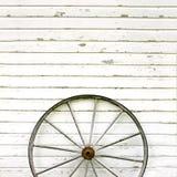 Antikes hölzernes Lastwagen-Rad auf rustikalem weißem Hintergrund Stockbilder