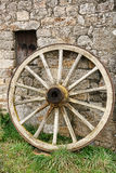 Antikes hölzernes Lastwagen-Rad gegen alte Steinwand Lizenzfreie Stockbilder