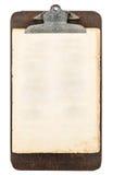 Antikes Klemmbrett mit dem Blatt Papier lokalisiert auf Weiß Stockfotografie