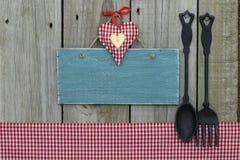 Antikes leeres blaues Zeichen mit Herzen, Ginghamtischdecke und Roheisenlöffel und -gabel Stockbilder