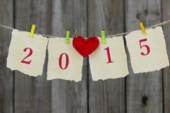 Antikes Papierzeichen des Jahres 2015 mit dem roten Herzen, das von der Wäscheleine durch hölzernen Zaun hängt Lizenzfreie Stockfotos