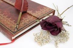 Antikes rotes Buch mit getrockneten roten Rosen stockfoto