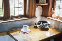 Antikes Telefon und Tasse Kaffee im alten Küchen-Satz Stockfotografie