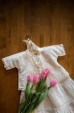 Antikes weißes Spitzetaufkleid mit rosa Tulpen Lizenzfreies Stockbild