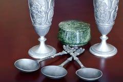 Antikes Zinn warf Weingläser, antike Metallsuppenlöffel und einen runden Kasten des grünen Steinserpentins auf einem braunen hölz stockfotografie