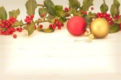 Antikisierte Weihnachtsverzierungen und -stechpalme auf hölzernem Hintergrund mit Raum oder -raum für Text, Wörter, Kopie. Stockfotos