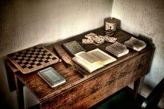 Antikt lekskrivbord med gamla lekar och forntida böcker Arkivbild