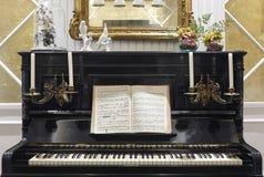 Antikt piano med stearinljus och den musikaliska ställningen Inomhus garnering Arkivbilder