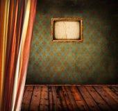 Antikt rum med grungeväggen och den tomma fotoramen Royaltyfri Bild