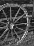 Antikt trävagnhjul mot träladugård arkivfoton