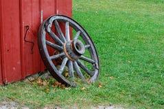 Antikt vagnhjul som lutar mot en röd ladugård arkivfoto