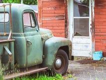 Antikviteten åldrades den gamla lastbilen framme av gammal riden ut byggnad royaltyfri bild