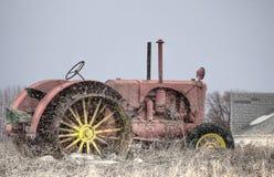 Antikviteten bleknade rött traktorsammanträde på dött gräs med att falla för snö royaltyfria bilder