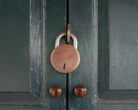 Antikviteten låste med den gamla rostade hänglåset på grön dörr arkivbilder