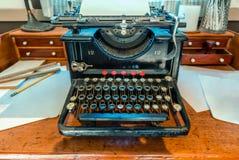 Antikviteten skrivmaskin med ett ark av vitbok står på ett trä arkivfoton