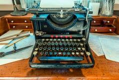 Antikviteten skrivmaskin med ett ark av vitbok står på ett trä royaltyfria foton