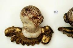 Antikviteten sned det barocka kerubängelhuvudet på väggen med auktionnummer royaltyfria bilder