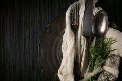 Antikviteten, tappningbestick med rosmarin och servetten dekorerade på en tabell royaltyfri bild