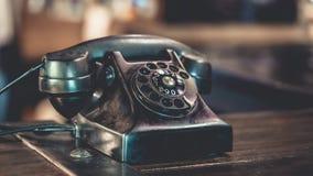 Antikvitetsvarttelefon på trätabellen royaltyfri bild