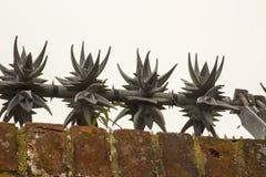 Antimuur die spinners met scherpe weerhaken op de bovenkant van een bakstenen muur beklimmen om indringers en inbrekers af te sch royalty-vrije stock afbeeldingen