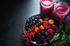 Antioxidant all berries fruit smoothie. In mason jat and fresh berries, food border background Royalty Free Stock Images