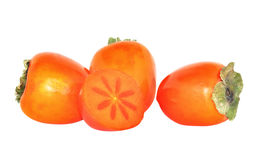 Antioxidant rich fresh persimmons. Fresh whole persimmons with one halved to show the star inside. Great source of antioxidants royalty free stock photography