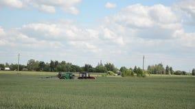 Antiparassitario dello spruzzo del trattore sul campo coltivato Acceleri la scena stock footage