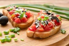 Antipasta italiano en el baguette cortado curruscante con las verduras Imágenes de archivo libres de regalías
