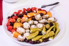 Antipasti Appetizer sweet cherry mini peppers stuffed with soft cheese feta on white plate. Antipasti Appetizer sweet cherry mini peppers stuffed with soft Royalty Free Stock Images