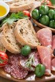 Antipasti italianos clasificados - carnes, aceitunas y pan de la tienda de delicatessen Fotos de archivo