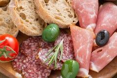 Antipasti italianos clasificados - carnes de la tienda de delicatessen, aceitunas y pan, cierre Fotografía de archivo libre de regalías