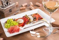 Antipasti mit Weißwein dienten in einer weißen Platte lizenzfreies stockfoto
