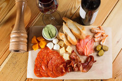 Antipasti platter on wooden surface. bottle and glass of wine. different snacks royalty free stock photos
