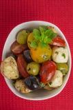 Antipasti salad with tomatoes and olives. Mediterranean antipasti salad with mozzarella balls, green and black olives and cherry tomatoes and some tiny-leafed Stock Photos