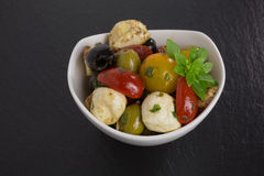 Antipasti salad with tomatoes and olives. Mediterranean antipasti salad with mozzarella balls, green and black olives and cherry tomatoes and some tiny-leafed Royalty Free Stock Images