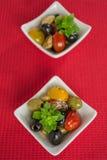 Antipasti salad with tomatoes and olives. Mediterranean antipasti salad with mozzarella balls, green and black olives and cherry tomatoes and some tiny-leafed Stock Image