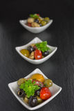 Antipasti salad with tomatoes and olives. Mediterranean antipasti salad with mozzarella balls, green and black olives and cherry tomatoes and some tiny-leafed Royalty Free Stock Photo