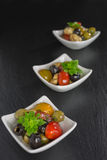 Antipasti salad with tomatoes and olives. Mediterranean antipasti salad with mozzarella balls, green and black olives and cherry tomatoes and some tiny-leafed royalty free stock image