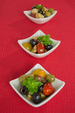 Antipasti salad with tomatoes and olives. Mediterranean antipasti salad with mozzarella balls, green and black olives and cherry tomatoes and some tiny-leafed royalty free stock photos
