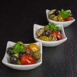 Antipasti salad with tomatoes and olives. Mediterranean antipasti salad with mozzarella balls, green and black olives and cherry tomatoes and some tiny-leafed Stock Photo