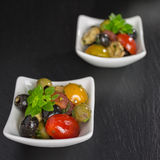 Antipasti salad with tomatoes and olives. Mediterranean antipasti salad with mozzarella balls, green and black olives and cherry tomatoes and some tiny-leafed Stock Photography